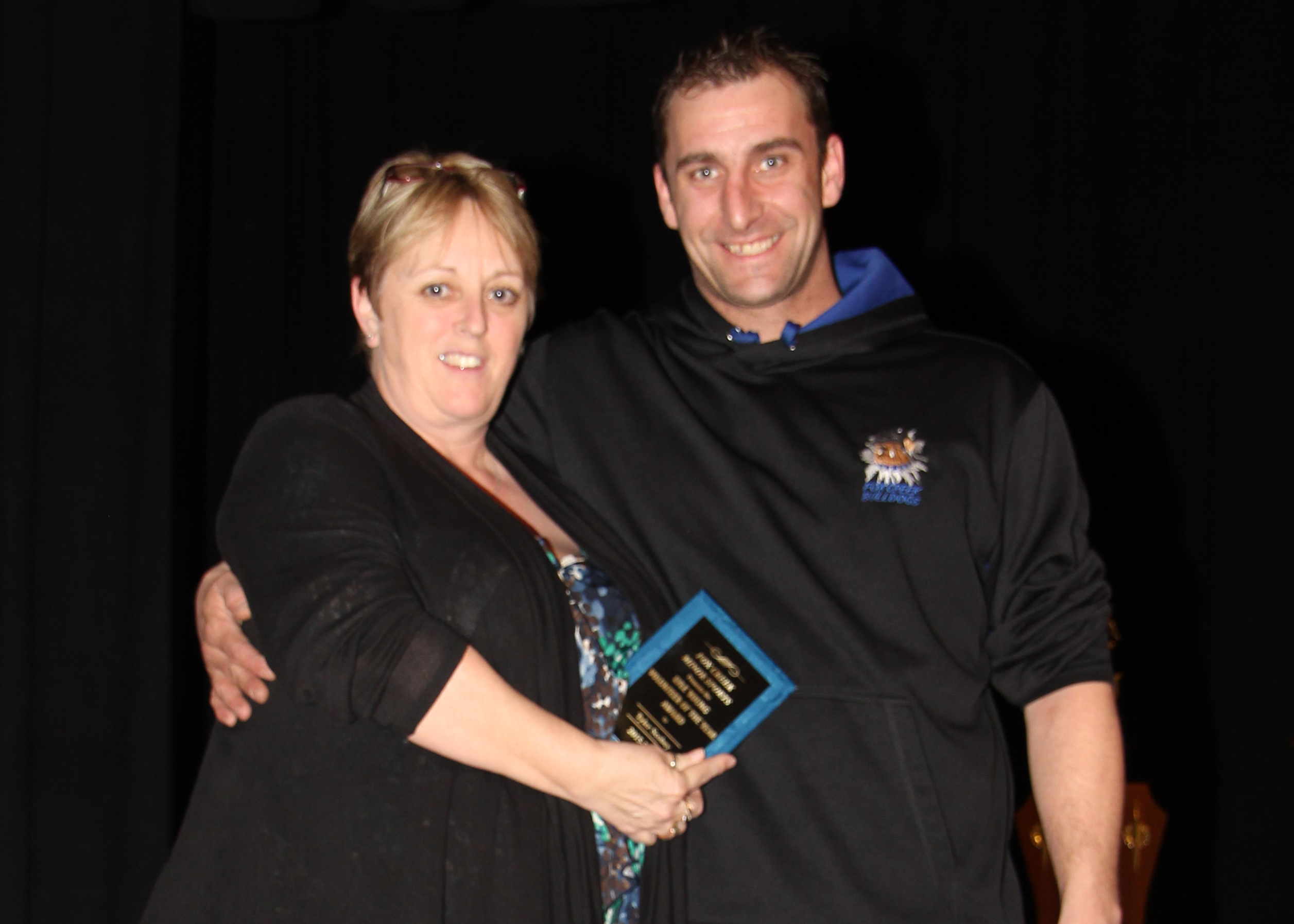 Brenda Burridge presents Tyler Scobey with the Lyle Young Volunteer of the Year Award